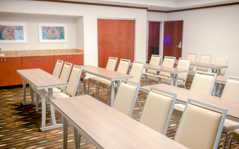 Meeting room with rows of rectangular tables with chairs