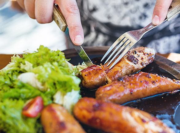Close up of silverware cutting through sausage on plate