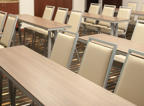 Rows of wooden rectangular tables with chairs in meeting room