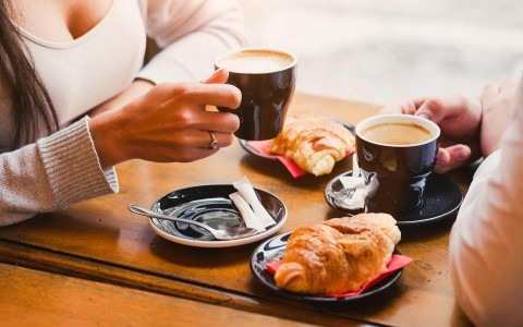 Couple enjoying cups of coffee and plates of croissants
