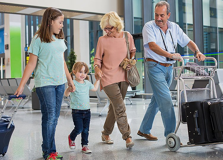 A couple with their two kids holding hands and pulling luggage
