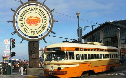 a boat wheel themed sign for the Fishermans Wharf of San Francisco and an old fashioned orange, brown and cream bus
