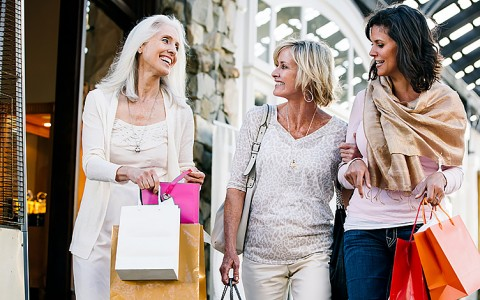3 women holding shopping bags and smiling at each other