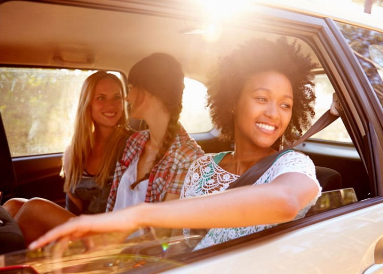 Three cheerful girls in the backseat of a car