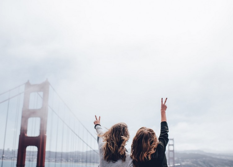 two woman looking at the bay bridge holding up peace signs