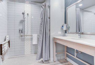 Hotel bathroom with a large sink area and a walk in shower with a shower seat
