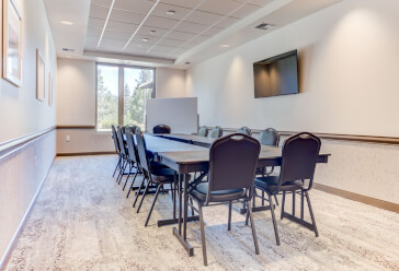 Meeting room with a conference table and 12 chairs, a whiteboard and flat screen TV