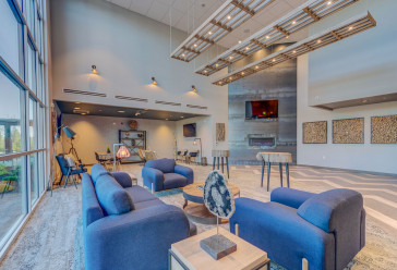 Stylish hotel lobby area with a blue couch, two blue chairs, tables, a fireplace and a flat screen TV