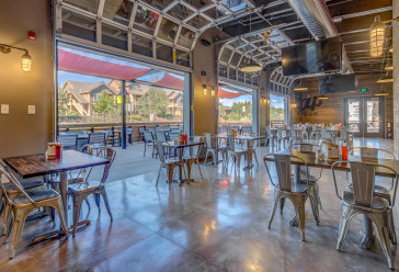 Zpizza and Tap room dining area with many wood tables, metal chairs and an outdoor seating area