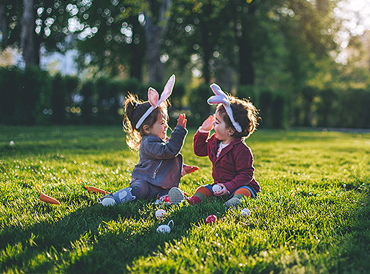 Two toddlers sitting in a field wearing bunny ears