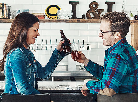 Man and woman clinking glasses of beer