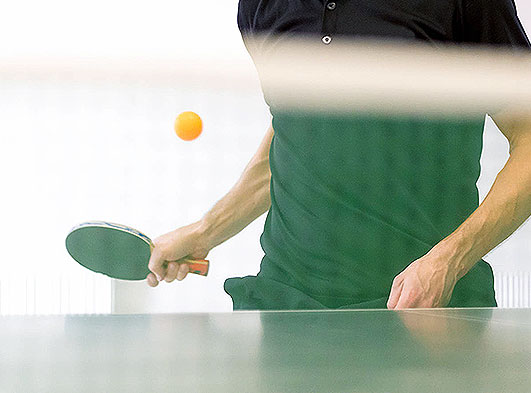Man holding ping pong paddle with ping pong ball