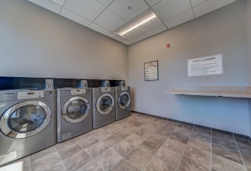 open concept laundry room with four washing machines