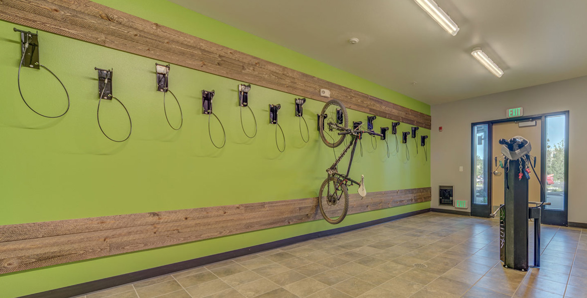 open space bike room with a bright green wall for hanging bicycles