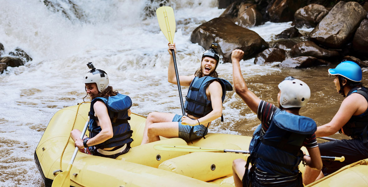 four people excited as they are white water rafting