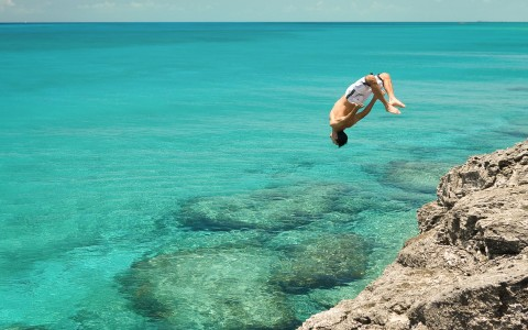 Man doing a back flip into ocean water