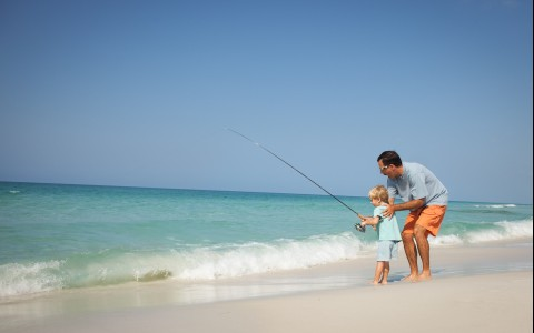 Man with small boy next to the ocean shore with fishing rod