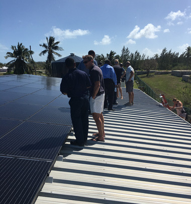 group of folks looking and studying solar panels