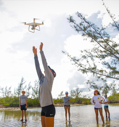 group of research scientist launching a drone in the air of marchy portion of the cape