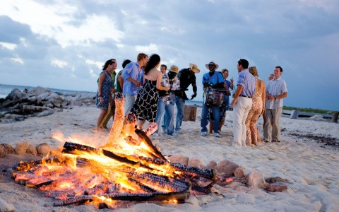 Group of people gathered at beach by bonfire