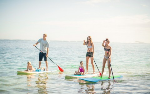 Family paddle boarding on the water