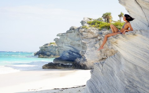 Woman sun bathing on rock that is overlooking the ocean
