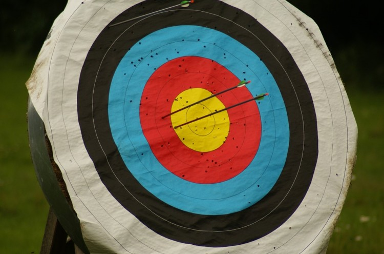 Archery bullseye with arrows in it