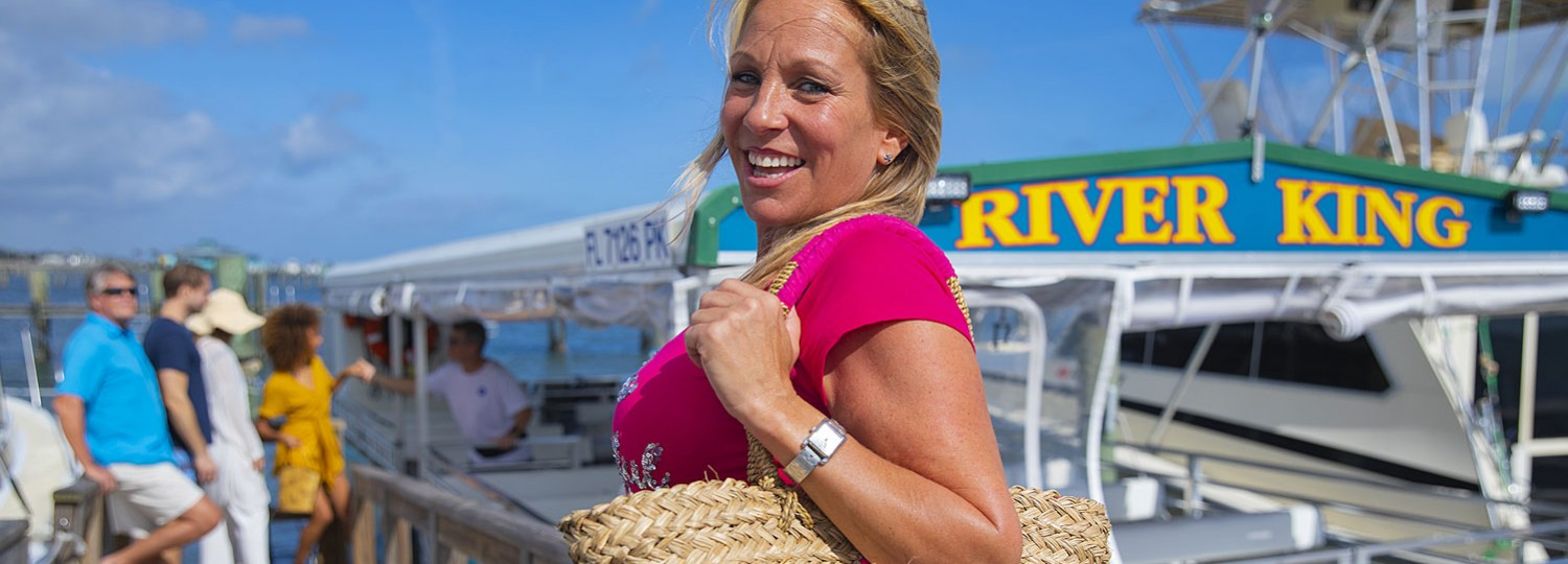 woman with hand bag getting on boat