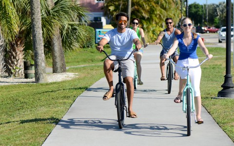 four friends riding beach cruiser bikes down the sidewalk