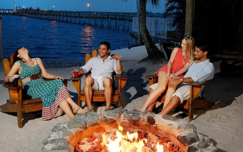two couples laughing by a waterfront bonfire