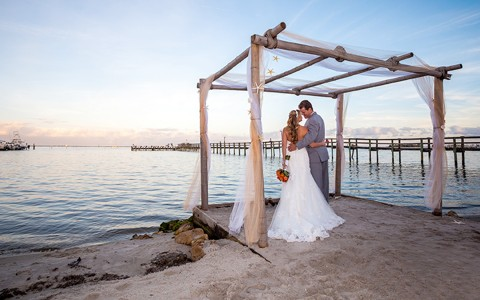 couple standing under a wedding canopy by the water