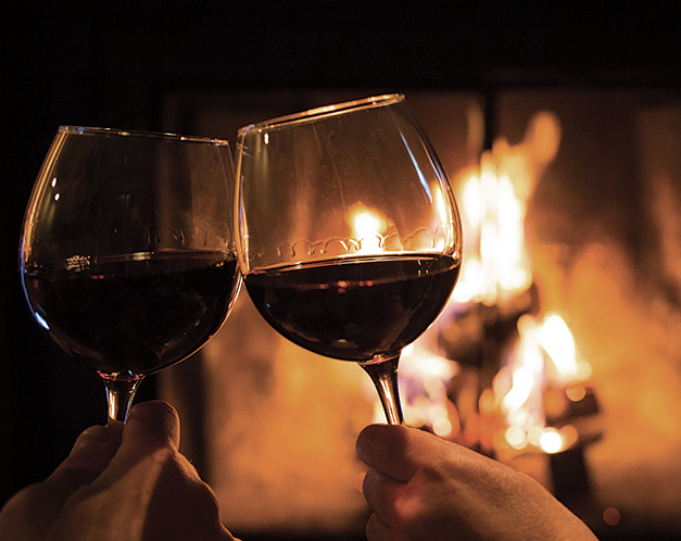 two glasses of wine in front of a fire