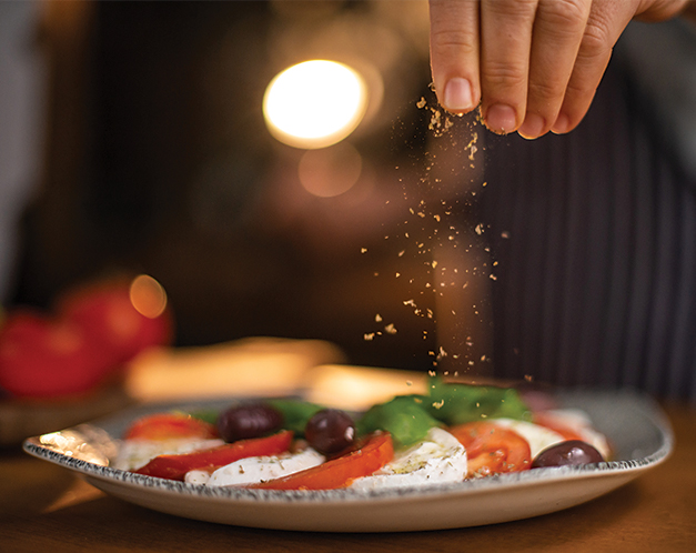 a person's hand sprinkling seasoning overtop tomato slices, mozzarella, and olives