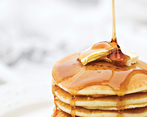 syrup being poured overtop a stack of pancakes