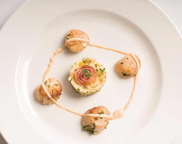 nicely decorated plate of scallops and a ball of rice
