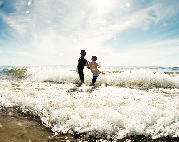 two people kicking at a wave crashing on the shore of the beach