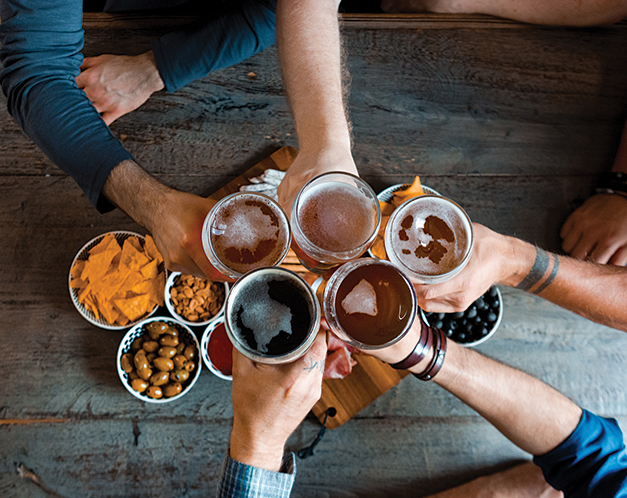 overhead view of a group of friends holding their beer glasses overtop a table for a cheers