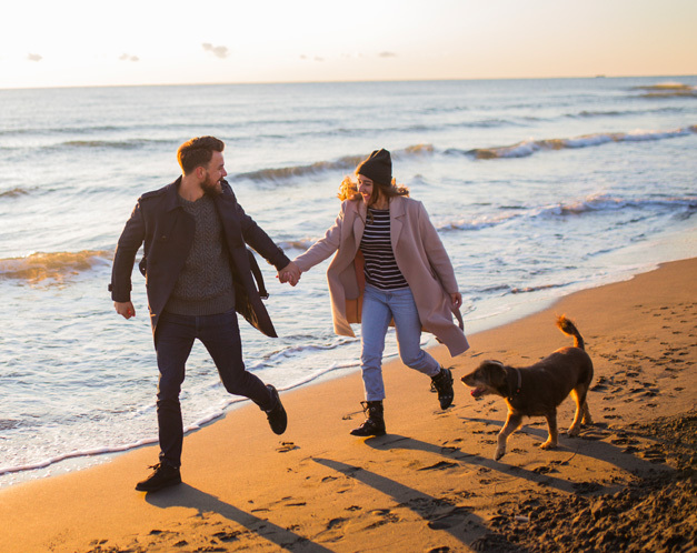 two people in winter clothing running on beach holding hands with dog next to them