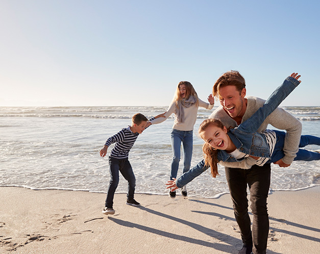 family in fall clothes playing on the beach