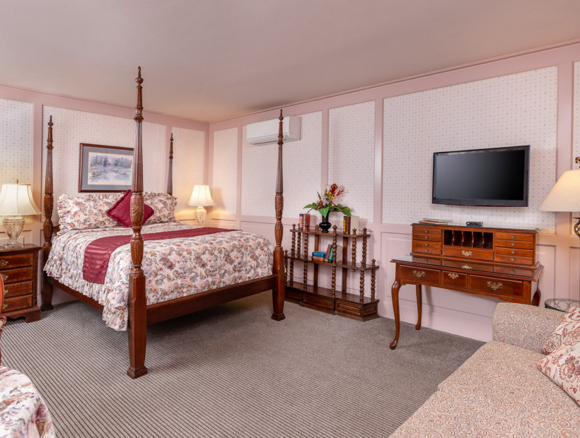 guest room with floral bedding, wooden bed frame and furniture, tv, and a couch