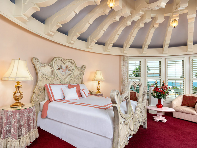 guest room with ornate moldings on the rounded ceiling, white linens, red carpet, and lounging chairs