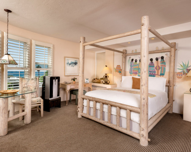 guest room with a white wooden bed frame, table, and nightstand,