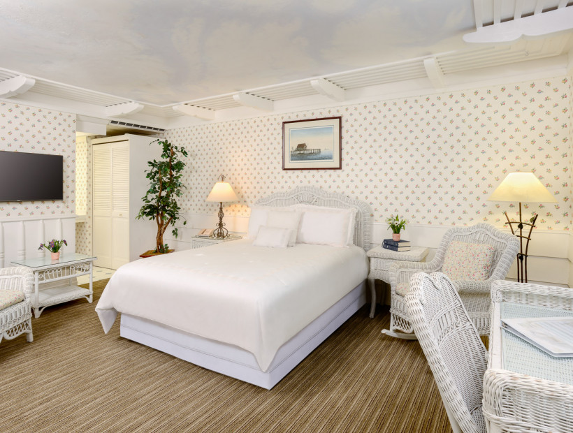 guest room with white furniture and white bed sheets