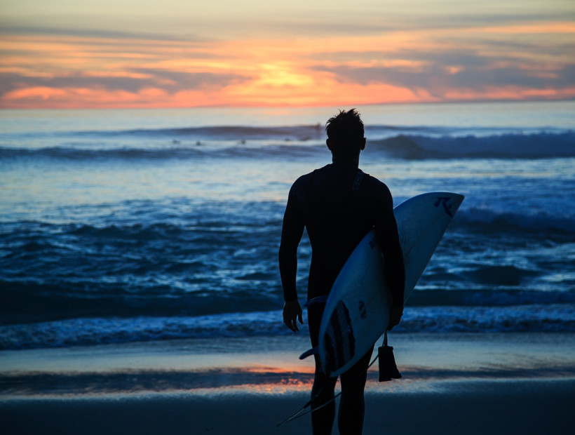 a surfer walking towards the ocean at sunrise