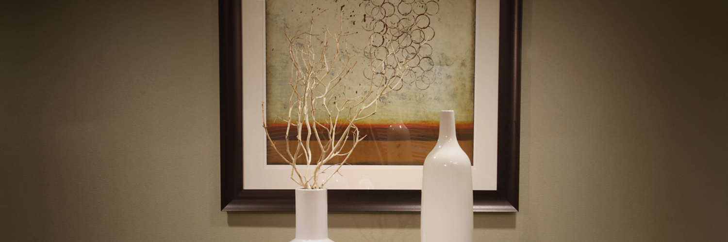 two white vases in front of abstract art piece