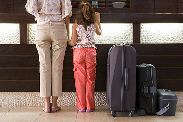 little girl and woman next to suitcases in front of front desk