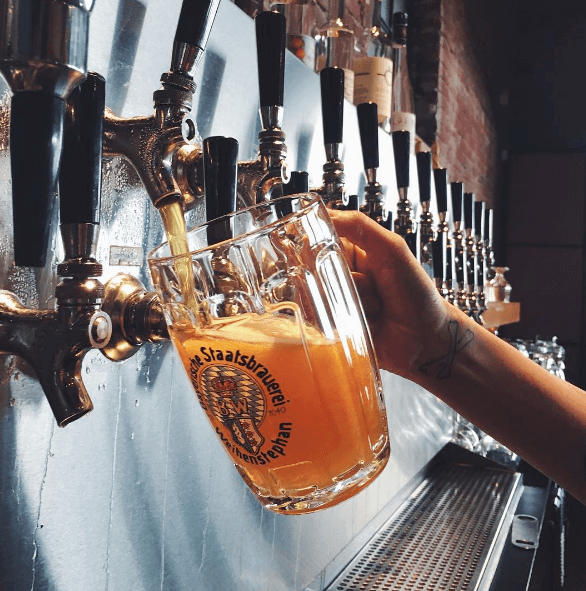 hand filling up pitcher with draft beer