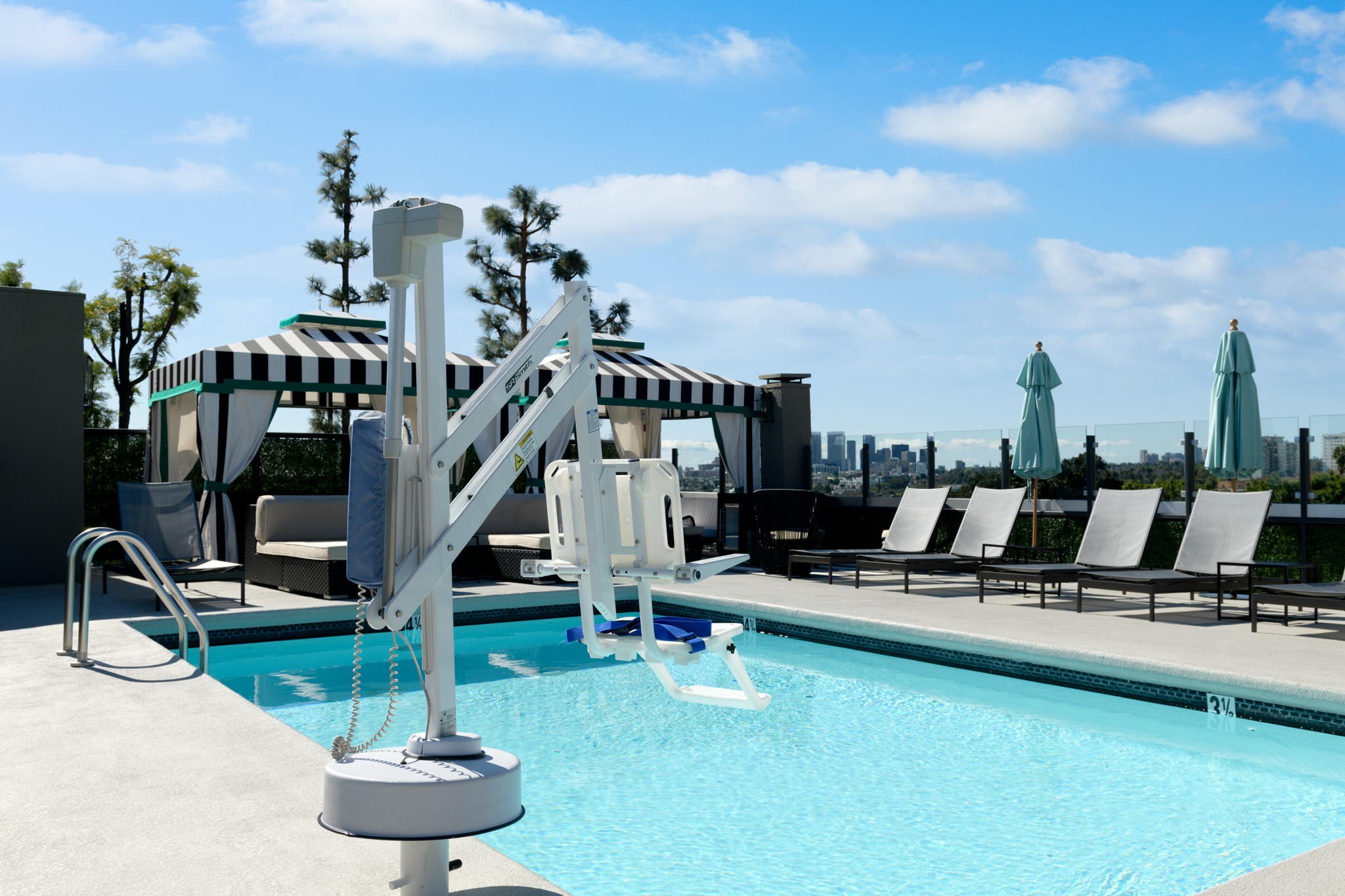 rooftop pool with ada lift, cabanas, and patio lounge chairs