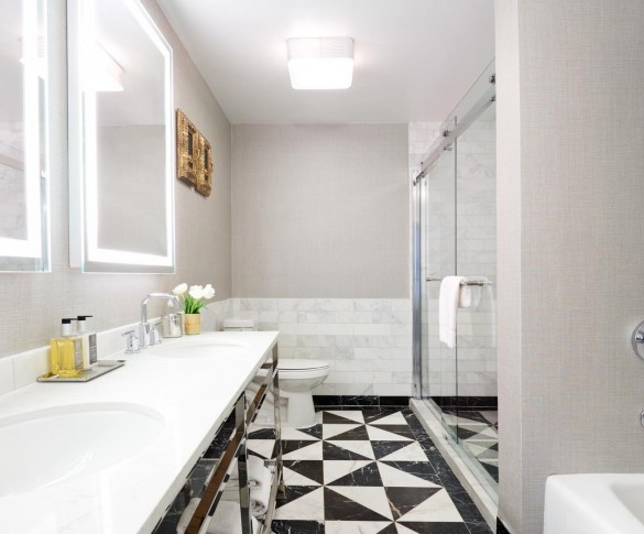 bathroom in the one bedroom suite with a large white vanity patterned tile shower and bath