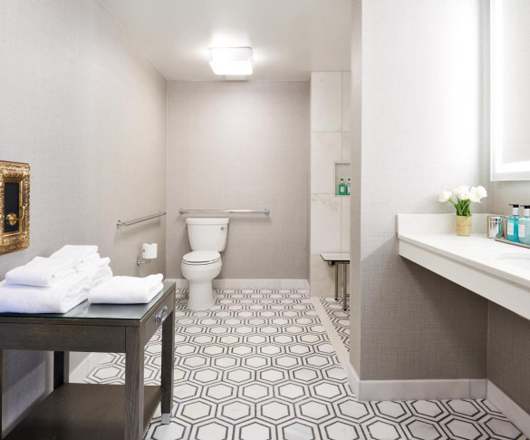 large bathroom in the ada suites with a patterned tile large vanity and table holding towels
